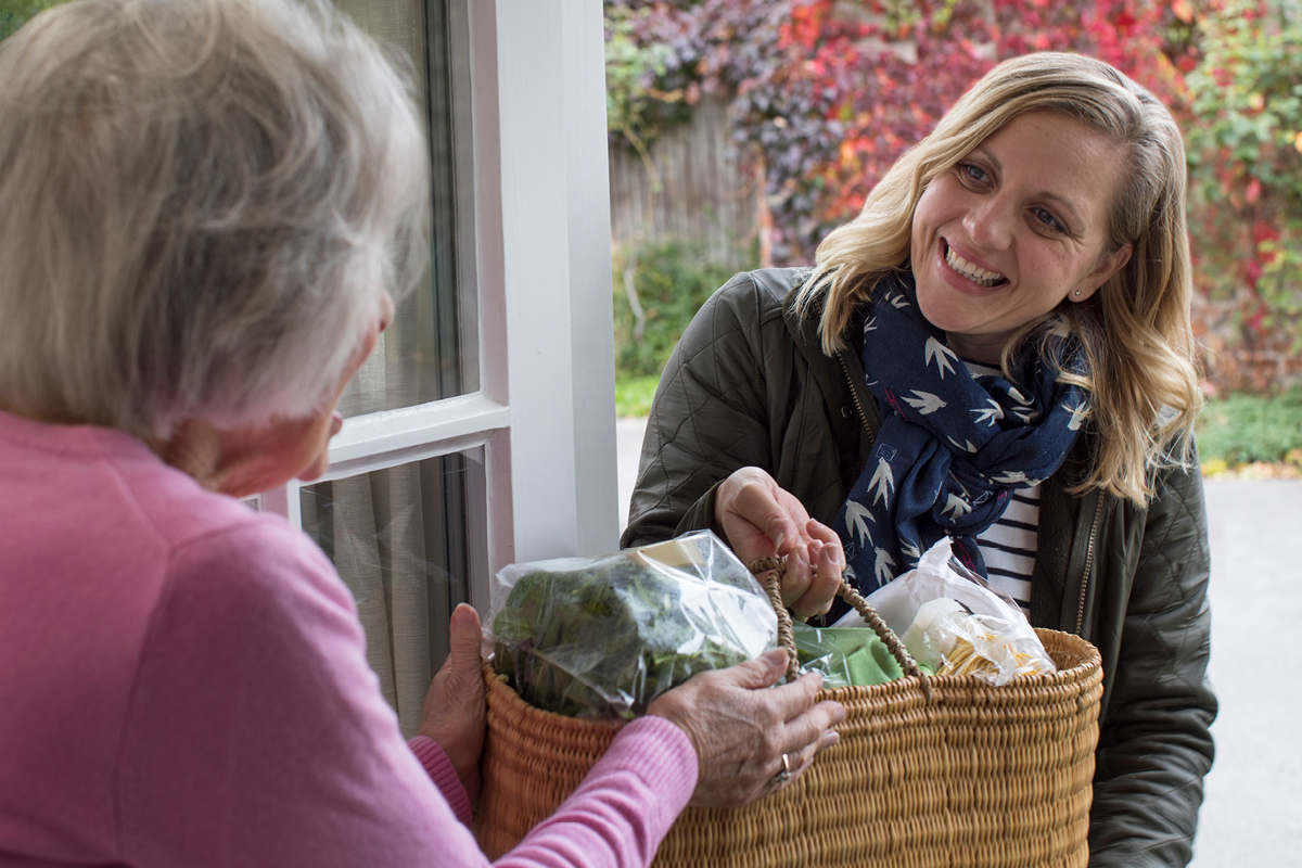 Woman delivering groceries to an elderly woman